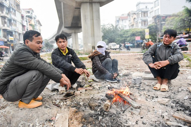 Do có mưa nhỏ, miền Bắc chìm trong giá rét, nhiệt độ cao nhất tại Hà Nội chỉ ở mức 16 độ C. Co ro trong tiết trời đông, nhiều lao động tự do đốt củi sưởi ấm giữa đường. (Ảnh: Hà Trang)