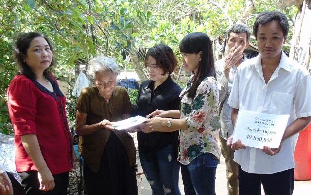 Phóng viên báo Dân trí cùng các nhà hảo tâm trao tiền bạn đọc hỗ trợ cho mẹ con bà Sáu