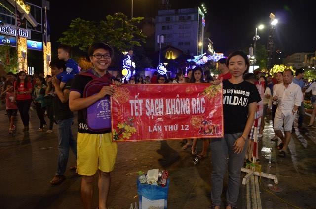 Một nhóm sinh viên tình nguyện đứng giữa đường hoa tuyên truyền, vận động người dân không xả rác.