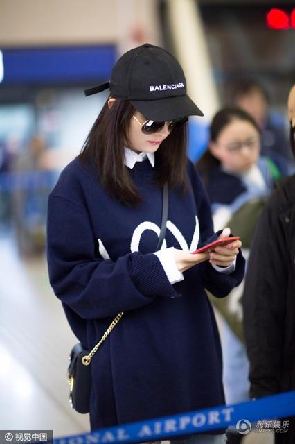 Cô tranh thủ kiểm tra lại điện thoại trong lúc chờ làm thủ tục. Phong cách thời trang trẻ trung của Dương Mịch khiến fan thích thú. Cô diện quần jeans rách, áo nỉ rộng và áo sơ mi.