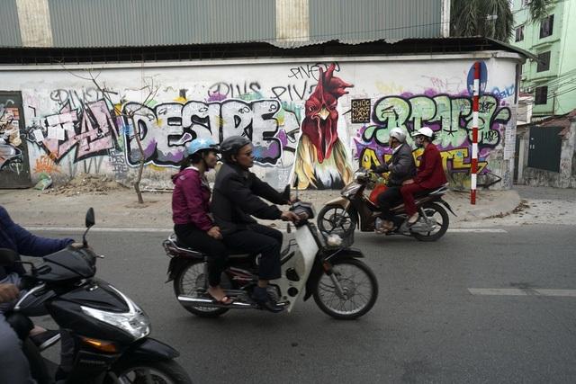 Tết Đinh Dậu, hình ảnh chú gà hiện diện khắp nơi ở Hà Nội. Cửa hiệu dán hình đôi gà trống, các tụ điểm dựng hình nộm gà khổng lồ... hay thậm chí có thể bắt gặp một khoảng tường có hình vẽ graffiti chú gà đang chúc mừng năm mới, rất sống động. (Ảnh: Hữu Nghị)
