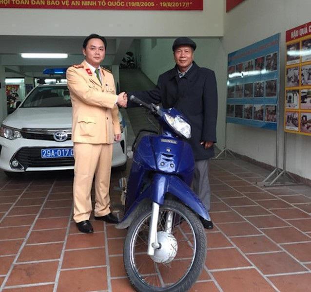 Ông Hoàng Điều xúc động nhận lại chiếc xe máy từ đại uý Nguyễn Tuấn Cường - Phó đội trưởng Đội CSGT số 2 Hà Nội.
