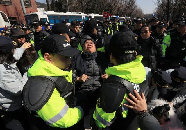 Một người ủng hộ bà Park đứng giữa rất đông các cảnh sát gần Nhà Xanh. (Ảnh: Reuters)