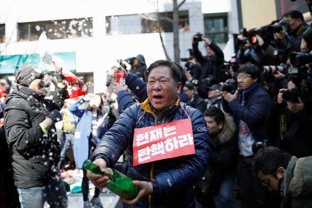 Một người đàn ông bật sâm-panh ăn mừng việc Tổng thống Park bị buộc thôi chức. (Ảnh: Reuters)