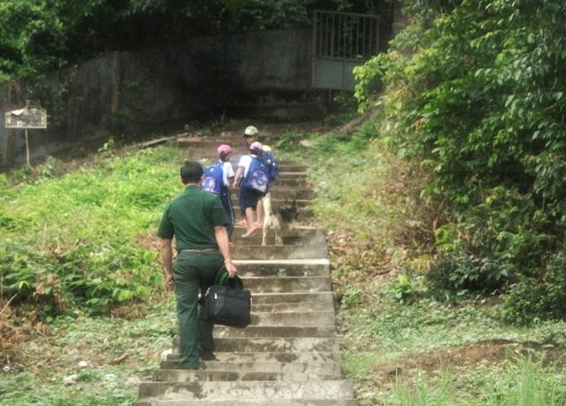 Thầy giáo và học trò cùng nhau bước qua từng bậc thang lên đỉnh núi để vào lớp học.