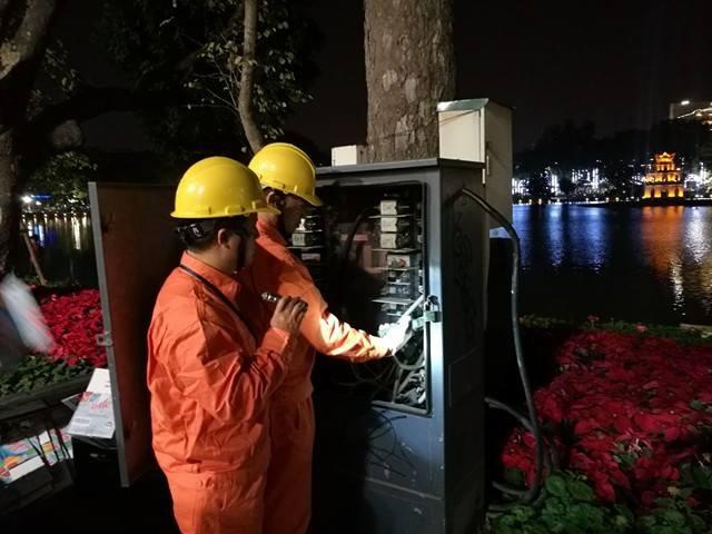 2 công nhân cty điện lực Hoàn Kiếm kiểm tra điện áp đảm bảo cấp điện an toàn