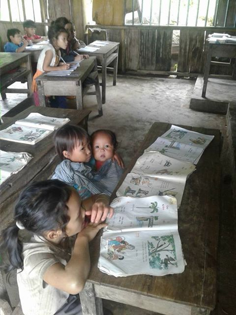 Hình ảnh Hồ Thị Nhung (lớp 2), địu em 8 tháng tới trường mà Dân trí đã đăng tải trước đó.