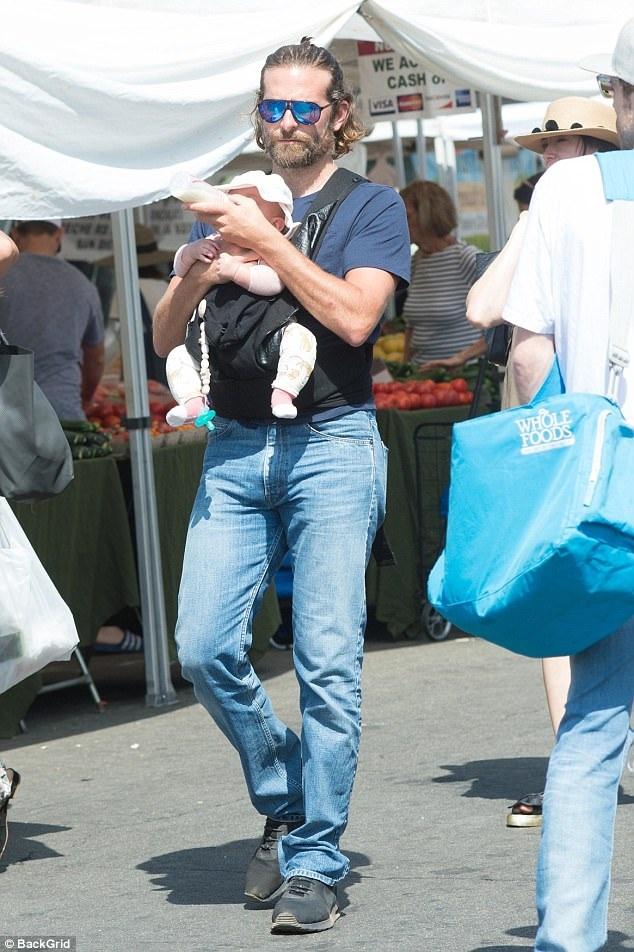 Bradley Cooper địu con gái 4 tháng tuổi Lea rất khéo léo, anh còn vừa đi vừa cho con bú bình sữa khá điêu luyện