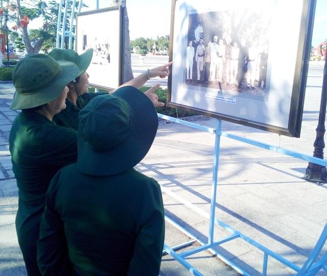 Những cựu chiến binh xem ảnh tư liệu.