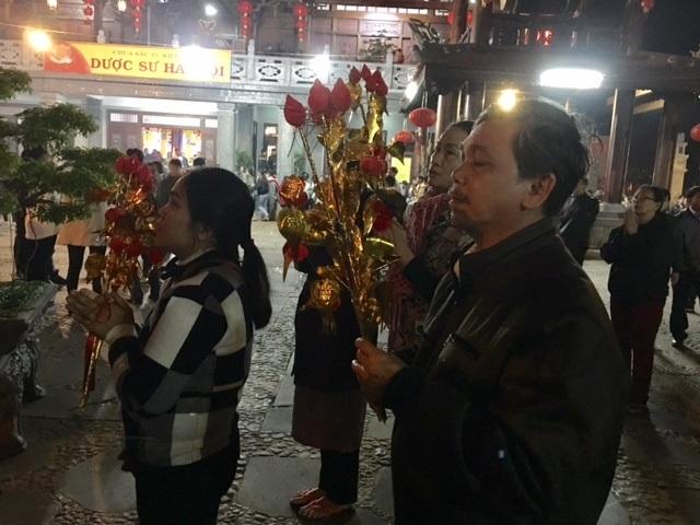 Người dân cầm cây phát lộc cúng bái Bồ Tát cầu mong thịnh vượng trong năm mới