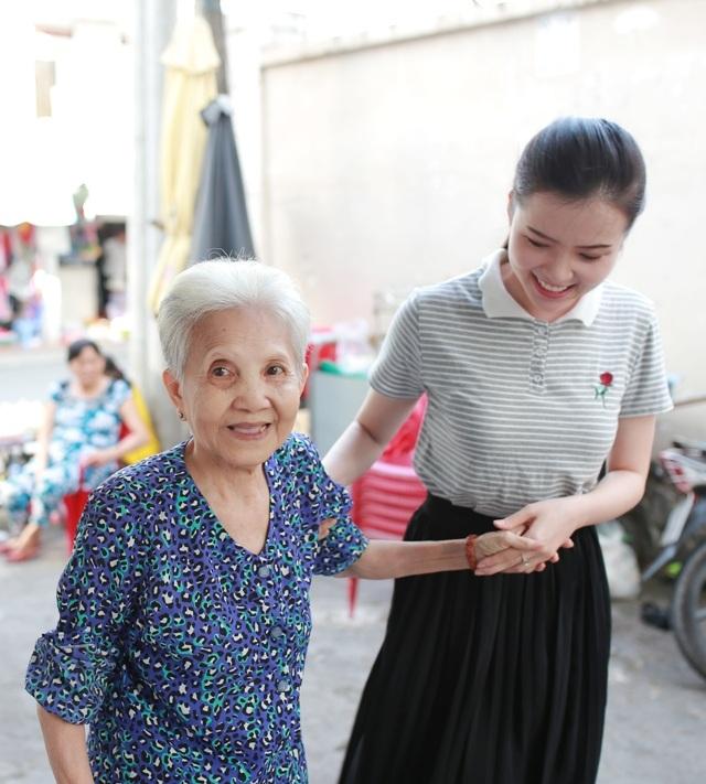 Cô Hoa khôi ân cần đón những cụ già, bày tỏ lòng kính mến của mình.
