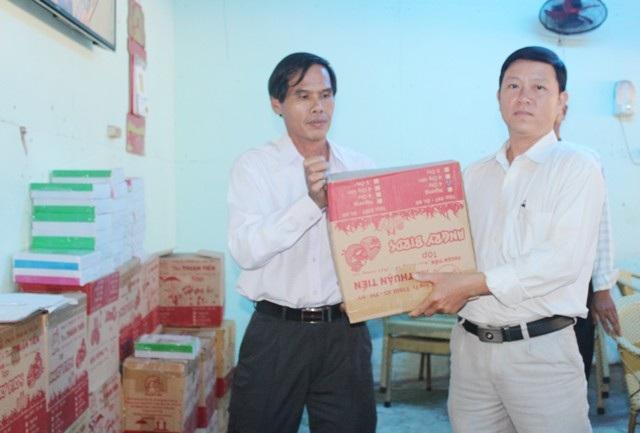 Ông Nguyễn Văn Định (trái) trao tập đến đại diện các đơn vị trường học để tặng các em học sinh nghèo nhân năm học mới.