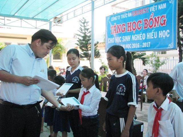 Ông Nguyễn Minh Hậu- Trưởng đại diện Công ty Grobest Việt Nam tại Bạc Liêu 2 trao học bổng cho các em học sinh ở huyện Hòa Bình.