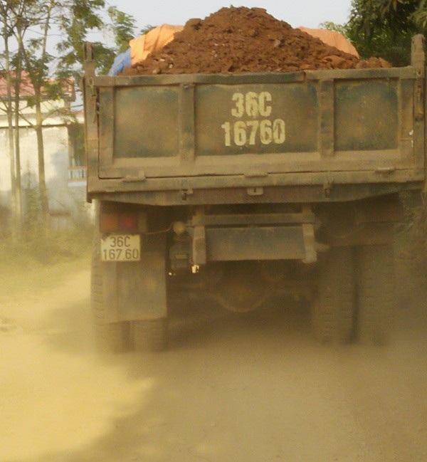Xe chở đầy đất không che chắn, đất rơi vãi xuống đường khiến bụi bay mù mịt