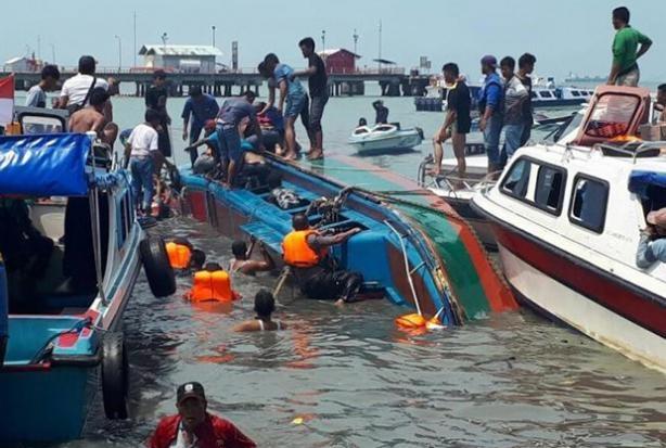 Các nhân viên cứu hộ tìm cách trục vớt các nạn nhân mắc kẹt bên trong tàu cao tốc bị lật ở Indonesia sáng 25/7 (Ảnh: EPA)