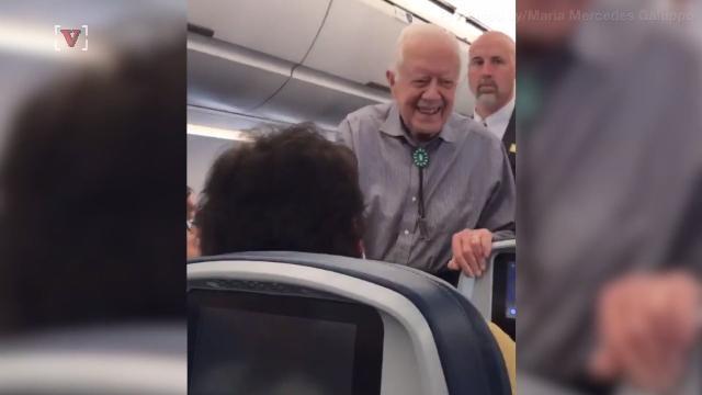 Cựu Tổng thống Mỹ Jimmy Carter vui vẻ bắt tay các hành khách trên chuyến bay. (Ảnh: CBS)