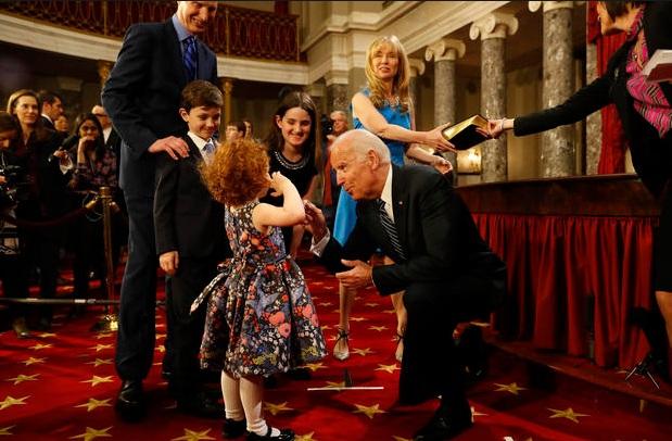 Ông Biden trêu đùa một bé gái, con của nghị sĩ Ron Wyden (Ảnh: Getty)