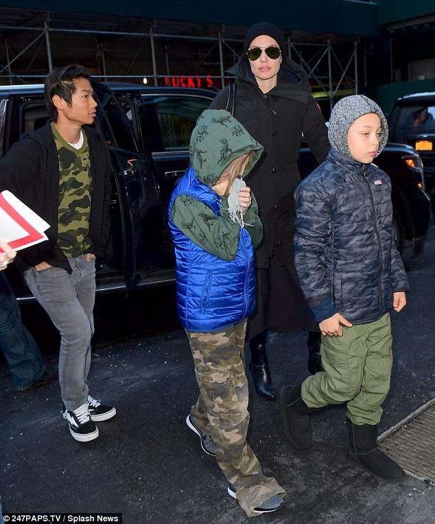 Con trai nuôi gốc Việt của Angelina Jolie mặc đồ rằn ri kết hợp áo khoác ngoài, quần jeans và giày thể thao. Pax Thiên giúp mẹ trông các em.