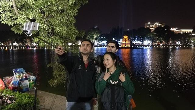 3 bạn trẻ người Palestine chụp ảnh tự sướng với bối cảnh phía sau là Tháp Rùa.