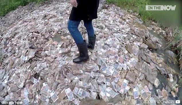 Một phóng viên đứng trên kho báu chứa đầy tiền