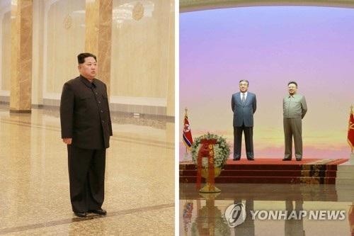 Nhà lãnh đạo Triều Tiên Kim Jong-un đứng trước tượng cha và ông nội. (Ảnh: Yonhap)