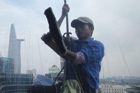 Một người thợ đang lau vết loang lổ của tấm kính.