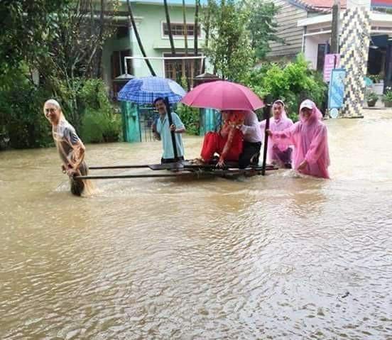 Cô dâu và chú rể ở Thị xã Hương Thủy được chở bằng xe ba gác qua đoạn nước lũ vào hôn trường (ảnh: facebook)