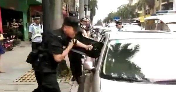 Cảnh sát đang nỗ lực đập vỡ cửa kính xe để cứu em bé mắc kẹt bên trong