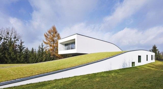 """Tại Ba Lan, kỹ sư Robert Konieczny đã thiết kế một căn biệt thự mẫu với tên gọi """"Ngôi nhà của tương lai"""". Công trình này đã thực sự gây ấn tượng với khách tham quan bởi kết cấu đặc biệt, các công nghệ tự động hiện đại và hơn hết chính là thảm cỏ xanh mướt mắt bao trùm lên gần như tòa bộ căn nhà."""