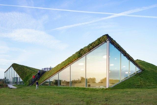"""Bảo tàng Biesbosch tọa lạc bên trong Công viên quốc gia, Hà Lan được thiết kế rất tài tình giúp nó có thể hòa mình với không gian thiên nhiên xung quanh. Được biết, hai kết cấu nhô lên làm bằng kính được lấy ý tưởng từ đôi cánh chim. Ngay phía sau """"đôi cánh"""" này chính là khu trung tâm của bảo tàng có có kết cấu vòng 6 cạnh."""