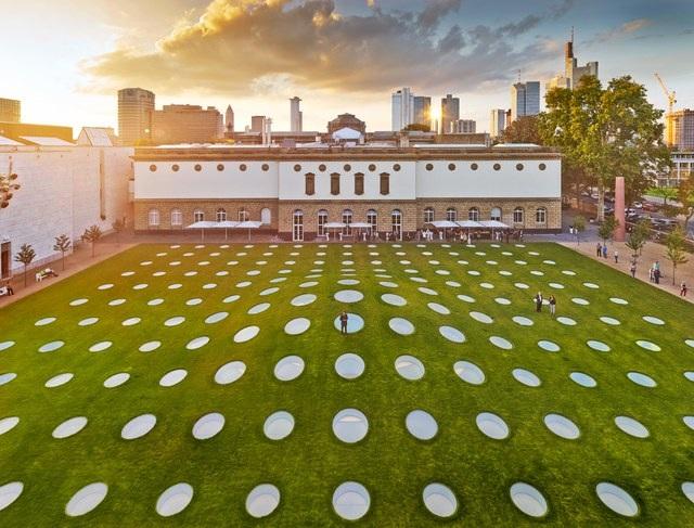 """Có lẽ sẽ không ít người thắc mắc tại sao trên thảm cỏ rộng lớn này lại đan xem những chấm tròn bằng kính """"khó hiểu"""". Thực ra, thảm cỏ mà chúng ta đang thấy chính là phần mái của một phòng trưng bày các tác phẩm nghệ thuật có giá trị lịch sử của Châu Âu thuộc bảo tàng Städel, Pháp nằm ngầm dưới lòng đất. Các tấm kính tròn trải đều trên thảm cỏ đóng một vai trò quan trọng trong việc mang ánh sáng và không khí thiên nhiên vào không gian bên trong của công trình."""