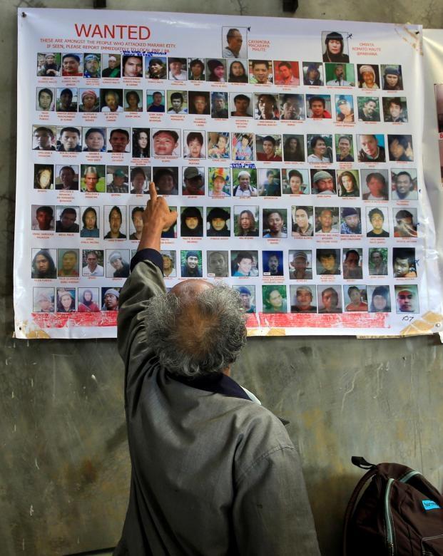 Cuộc xung đột tại Marawi tính đến nay đã bước sang tháng thứ 2. Theo thống kê mới nhất của giới chức Philippines, 280 tay súng khủng bố đã bị tiêu diệt kể từ khi cuộc xung đột bắt đầu hôm 23/5. Trong ảnh: Người dân Philippines chỉ vào ảnh của một thành viên trong nhóm Maute - nhóm phiến quân tấn công thành phố Marawi hôm 23/5.