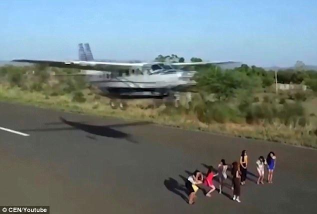 Những cô gái cúi đầu xuống khi máy bay lướt ngay phía trên. (Ảnh: CEN)
