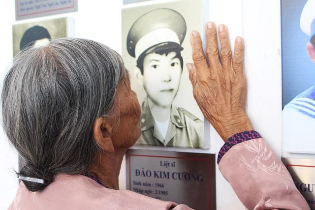 Mẹ liệt sĩ Đào Kim Cương (Hà Tĩnh) run run đặt bàn tay lên di ảnh con tại Khu trưng bày kỷ vật về các chiến sĩ Gạc Ma (Ảnh: Viết Hảo)