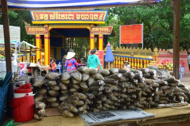 """Đến chùa Dơi, chúng tôi ghi nhận không khí rất vắng vẻ bởi số lượng du khách không đông như các năm trước. Dù trước cổng chùa đã có tấm biển không mua bán trước cổng nhưng người bán hàng vẫn bày hàng hóa ra bán ngay cổng chùa, chiếm cả lối đi vào chùa, trong đó có rất nhiều người bán các loại thực phẩm """"mặn"""" như các loại cá khô, mắm…"""