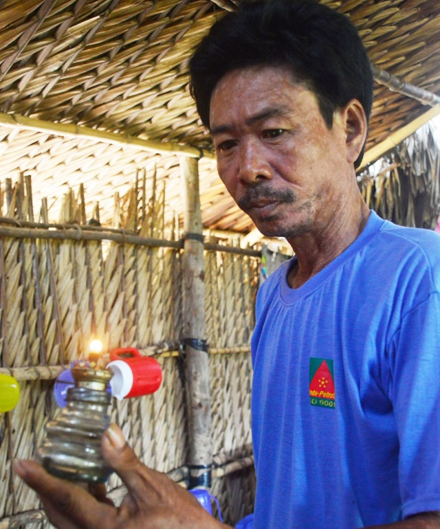 Một người dân thắp đèn dầu vì chưa có điện sử dụng.