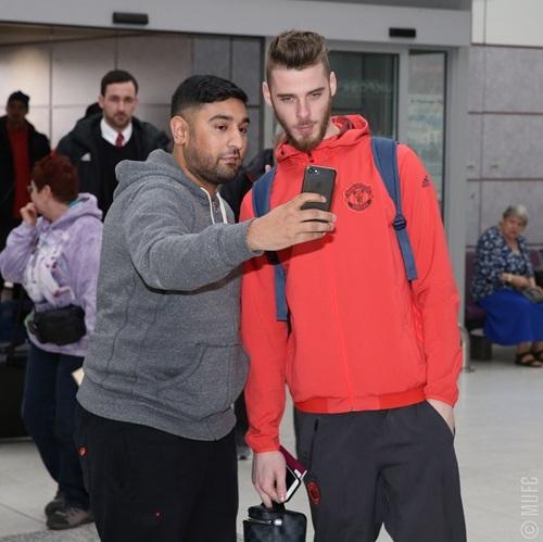 De Gea (phải) chụp ảnh cùng người hâm mộ ở sân bay Manchester trước giờ lên máy bay tới Nga