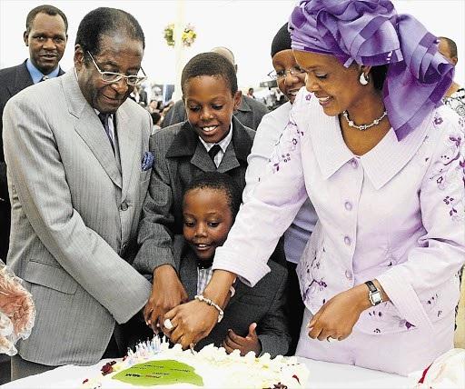 Tổng thống Mugabe cùng vợ và 2 con trai cắt bánh sinh nhật tuổi 80 của ông năm 2004. (Ảnh: Reuters)