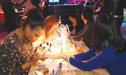 Hai cô thợ nail đang vẽ móng cho khách tại một tiệm nail ở Miami - Florida.