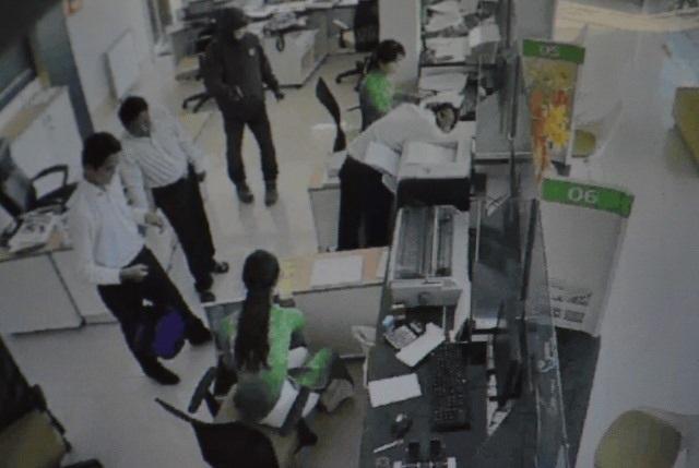 Hình ảnh trích xuất từ camera an ninh cho thấy người mặc đồ đen đang chĩa súng uy hiếp các nhân viên ngân hàng.