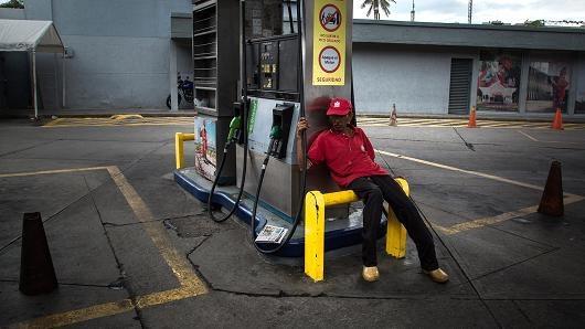 Một nhân viên ngồi thất thần tại trạm xăng Petroleos de Venezuela tại Caracas, Venezuela. (Nguồn: Wil Riera   Bloomberg   Getty Images)