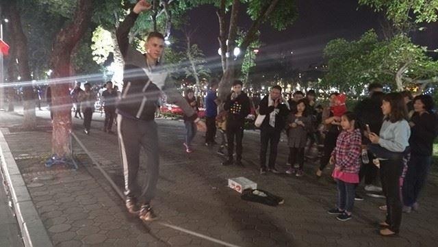 Một nghệ sỹ đường phố biểu diễn đi thăng bằng trên dây mua vui cho du khách.