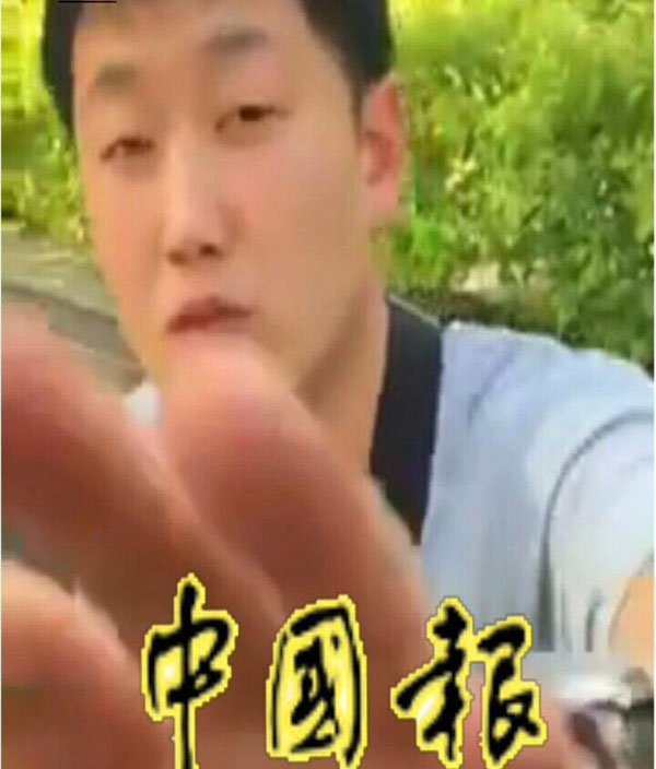 Người đàn ông đã lấy tay che màn hình khi biết đang bị ghi hình. (Ảnh: China Press)