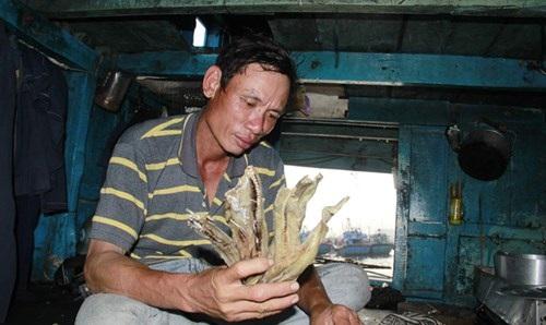 Anh Phạm Văn Sơn (huyện Đức Phổ, tỉnh Quảng Ngãi) gói ghém cá khô đem về làm quà Tết cho gia đình. Ảnh: Thanh Trần