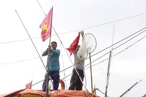 Ngư dân thay lá cờ Tổ quốc mới cho con tàu đón năm mới. Ảnh: Thanh Trần