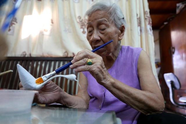 Ở tuổi 88, bà Vũ Thị Thanh Tâm vẫn cặm cụi làm thiên nga bông mỗi dịp Trung thu đến. Trong khu phố cổ Hà Nội, bà là người cuối cùng còn làm món đồ chơi thủ công truyền thống từng là mơ ước của các bé gái thời bao cấp này. (Ảnh: Quý Đoàn)