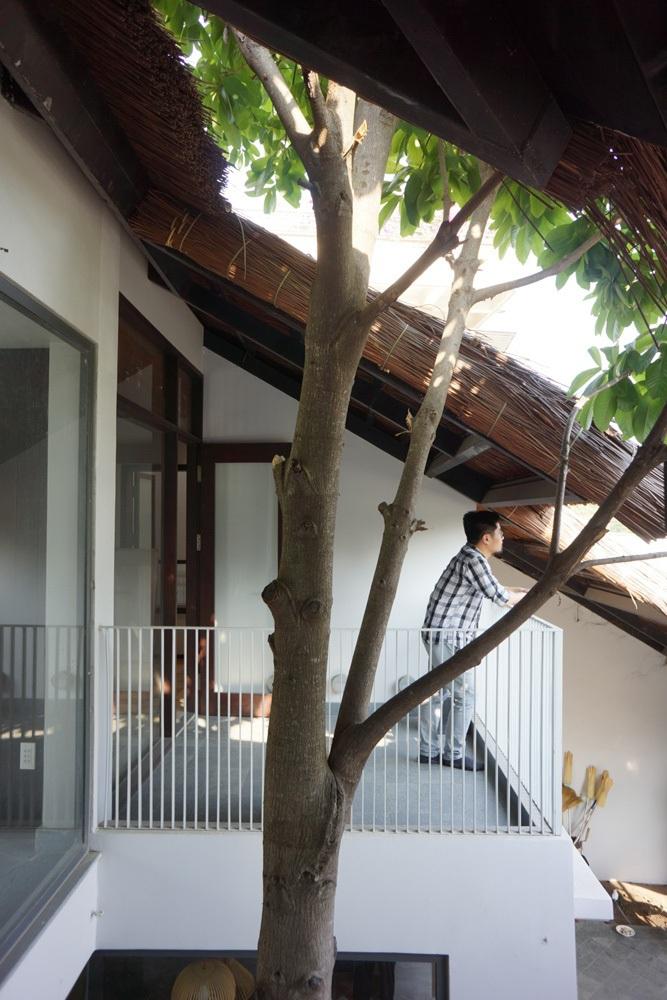 Căn nhà có lối kiến trúc khoáng đạt, kế thừa kinh nghiệm truyền thống nhờ lớp không gian chuyển tiếp trong – ngoài. Hệ lam gỗ chạy dọc hành lang tạo bề mặt cong chắn nắng Tây Nam cùng với các thớt mái lá dốc, vươn rộng hòa vào sân vườn.