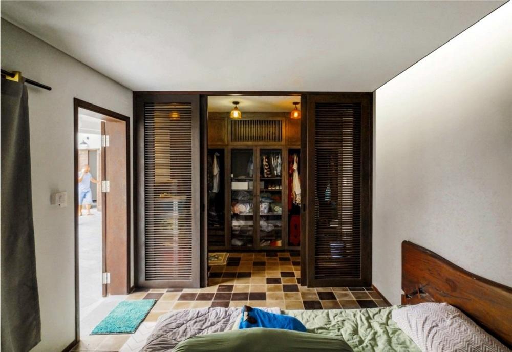 Phòng ngủ được bố trí tông màu ngẫu hứng, vừa sử dụng gạch hoa lát sàn, vừa sắp đặt các đồ dùng bằng gỗ và sử dụng kết hợp bức vách dạng cửa chớp khiến không gian trở nên lạ mắt nhưng không kém phần ấm cúng.