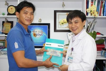 Ông Lê Minh Hiển, Trưởng phòng Công tác Xã hội trao tiền bạn đọc Dân trí giúp gia đình anh Hưng