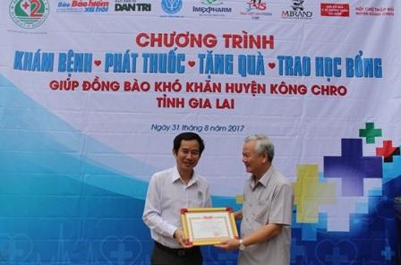 Đại diện địa phương (bên phải) trao bảng tri ân đến đoàn từ thiện